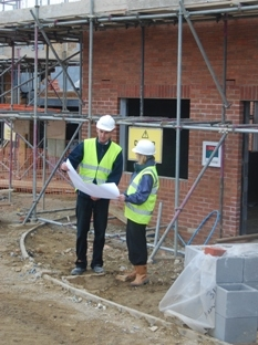 Image of two surveyors looking at plan